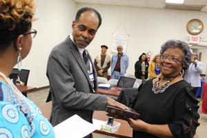 Joined with his wife, Charity, Rodger Scott takes his oath of office for his seat on the Aberdeen School Board from Sharion Gladney before last week's meeting.